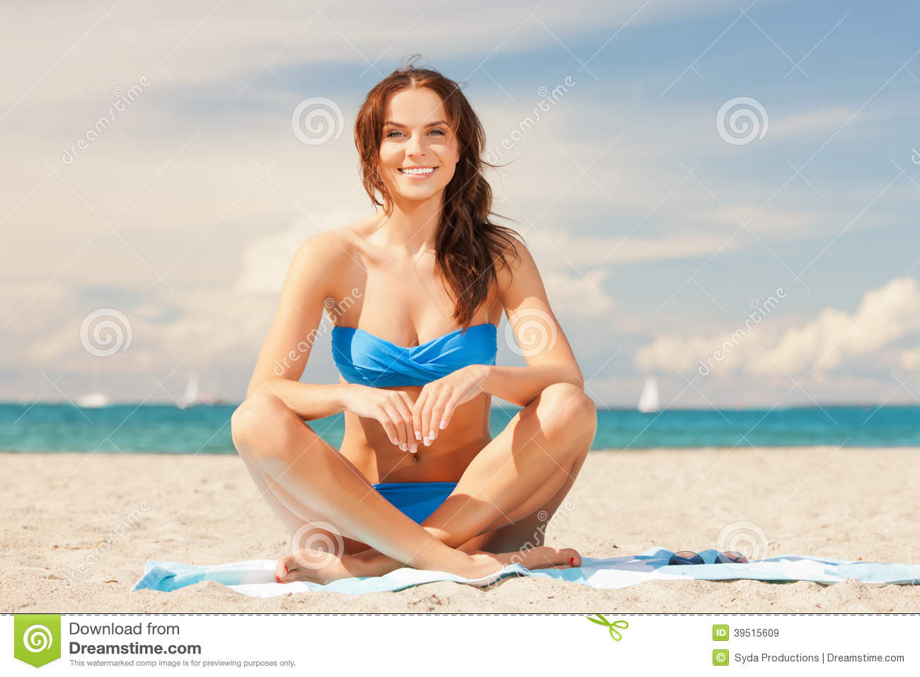 Happy smiling woman sitting on a towel