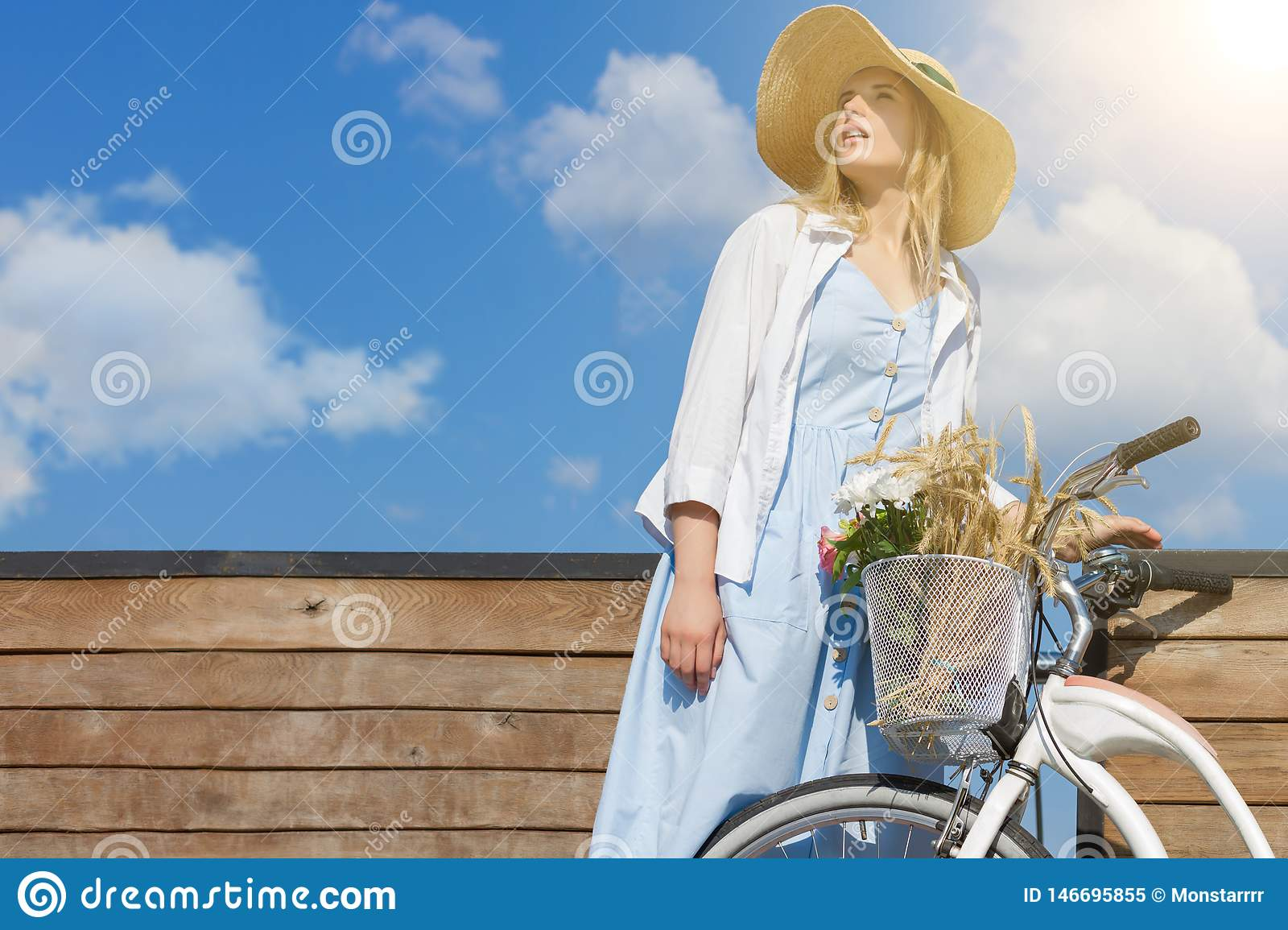 Woman in retro dress straw hat close to bicycle with basket of flowers