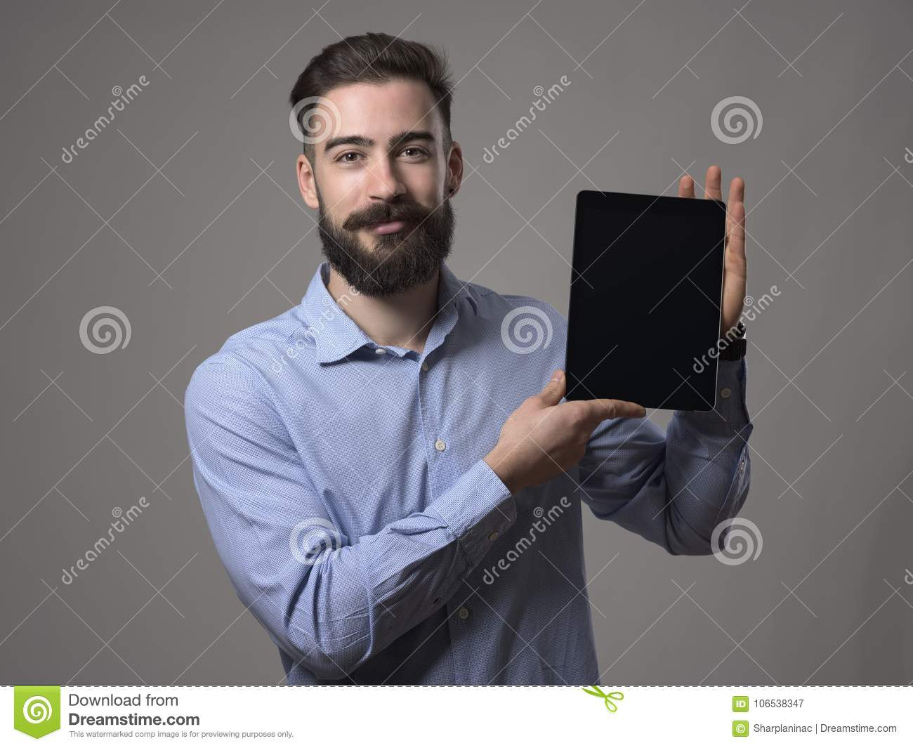 Happy smiling young bearded business person or programmer showing tablet screen with blank space for advertising