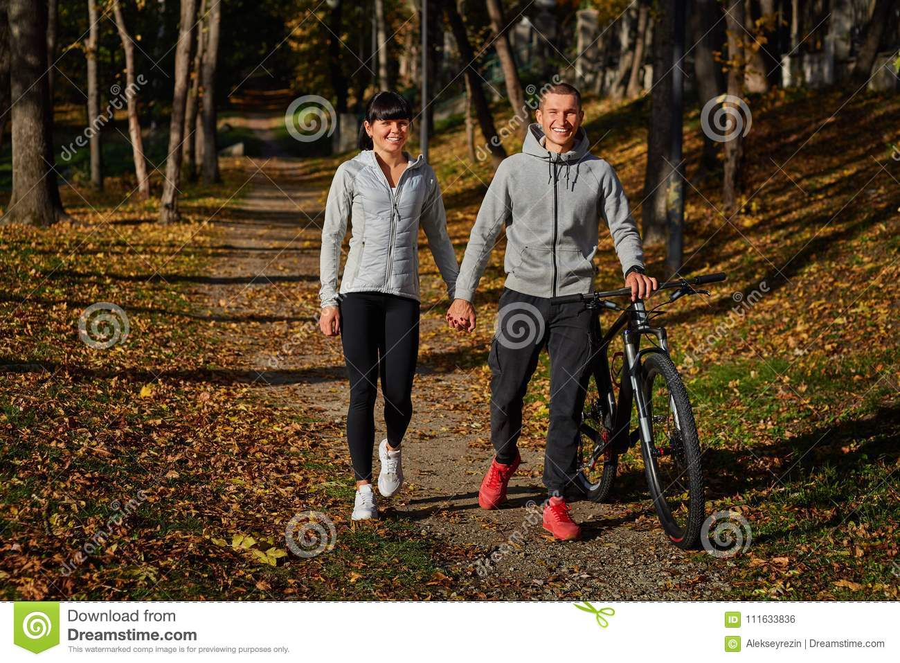 Happy Young Couple Going For A Bike Ride On An Autumn Day In The