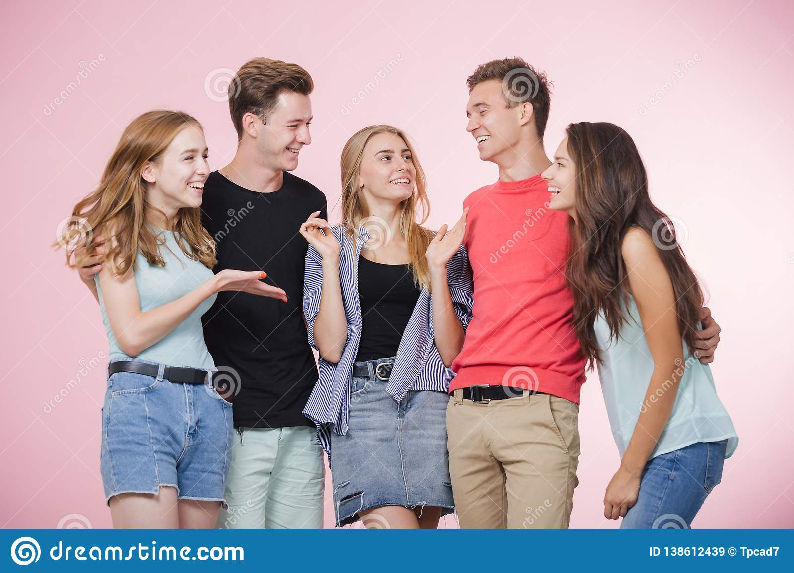Happy smiling young group of friends standing together talking and laughing. Best friends