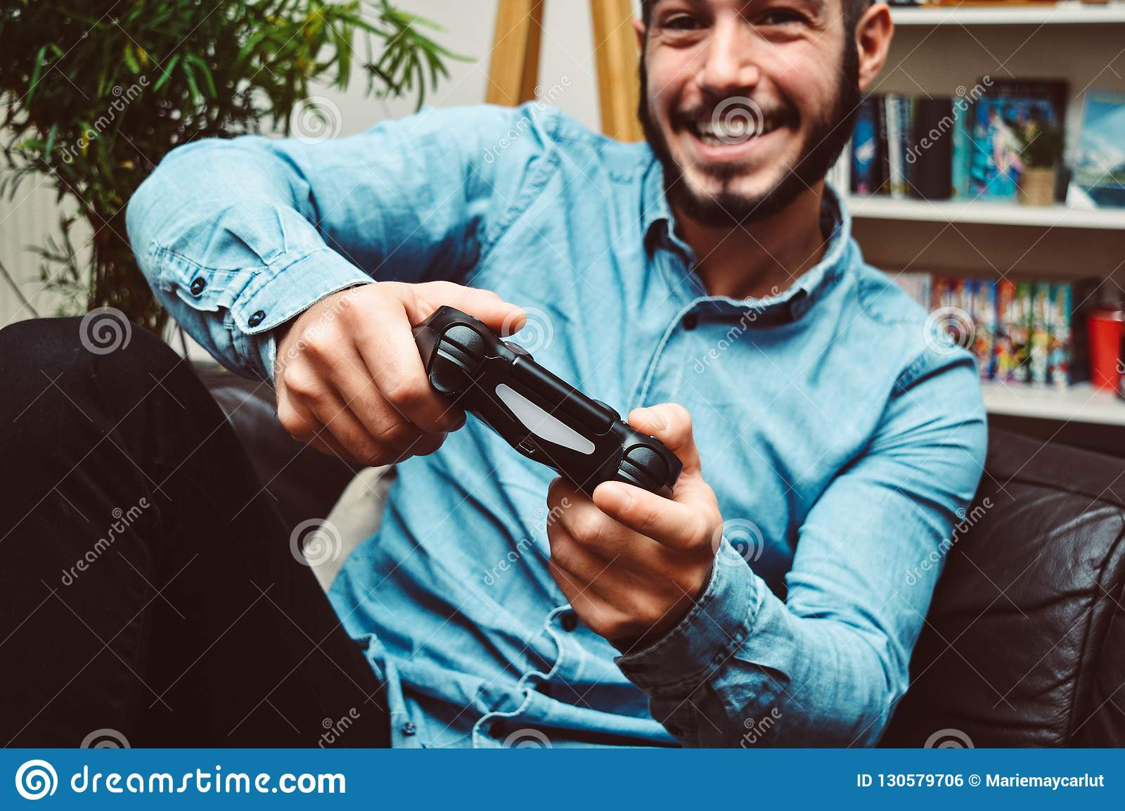 Happy smiling young handsome man playing video games and having fun at home