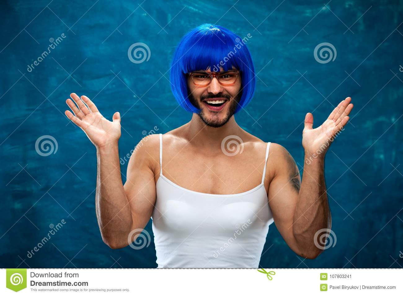 Happy smiling young man wearing blue wig and female cloth. Cross dressing  male person posing on blue background. a3064e599