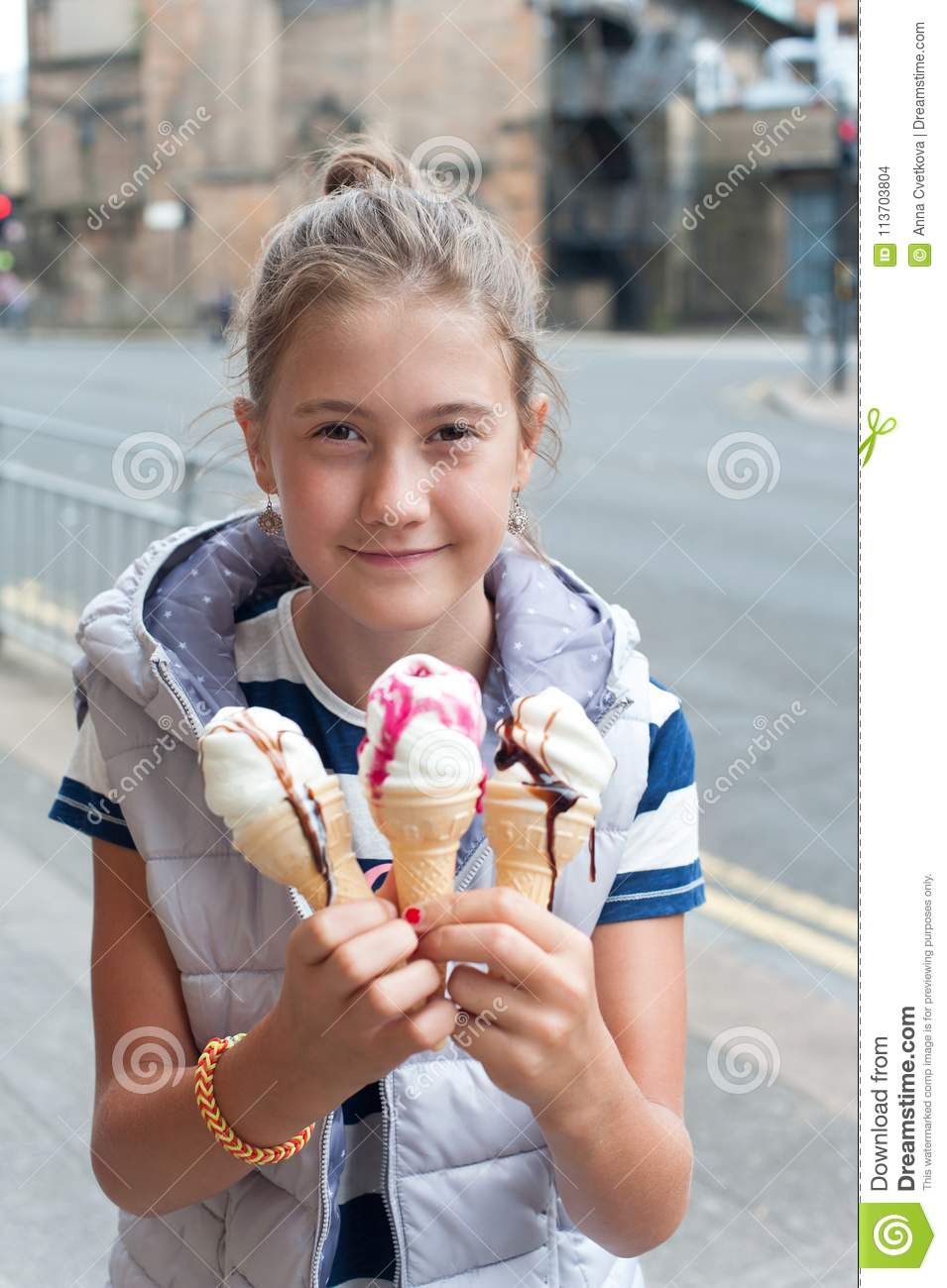 Happy smiling young pretty girl with many ice-cream. Outdoors image.