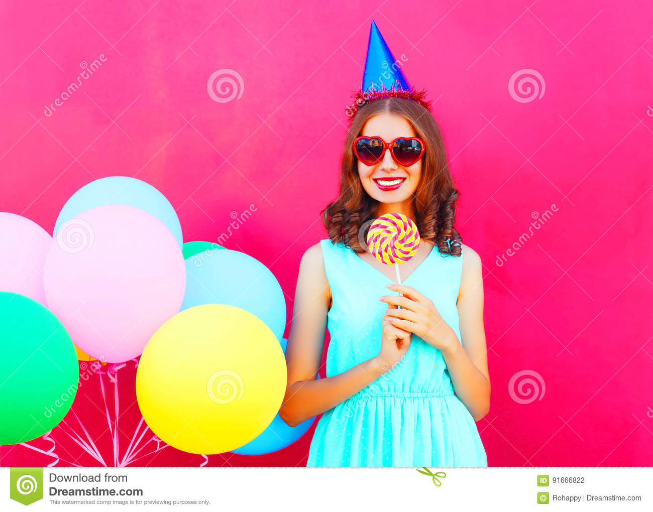 Happy smiling young woman in a birthday cap with an air colorful balloons and lollipop on stick over pink background