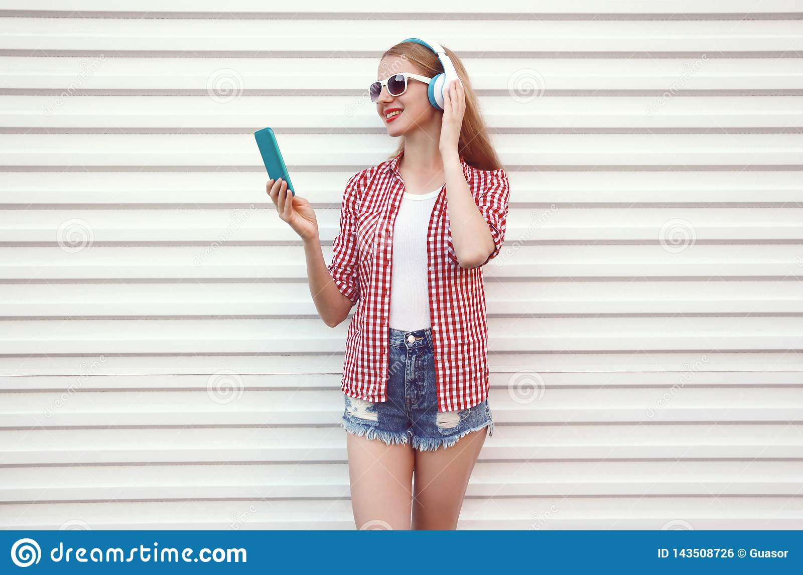 Happy smiling young woman in headphones with smartphone listening to music wearing checkered shirt, shorts on white