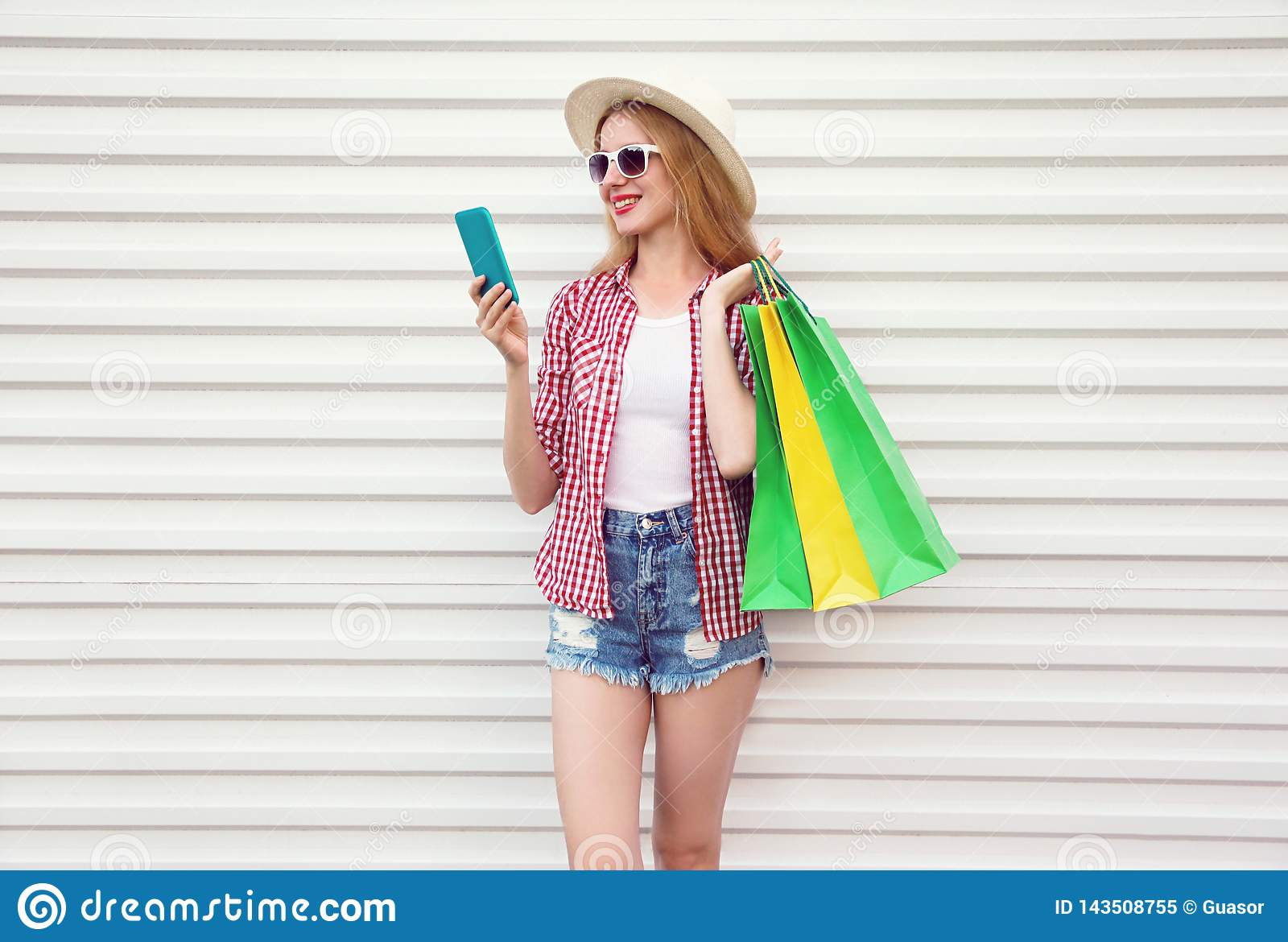 Happy smiling young woman with phone, holding colorful shopping bags in summer round straw hat, checkered shirt, shorts on white