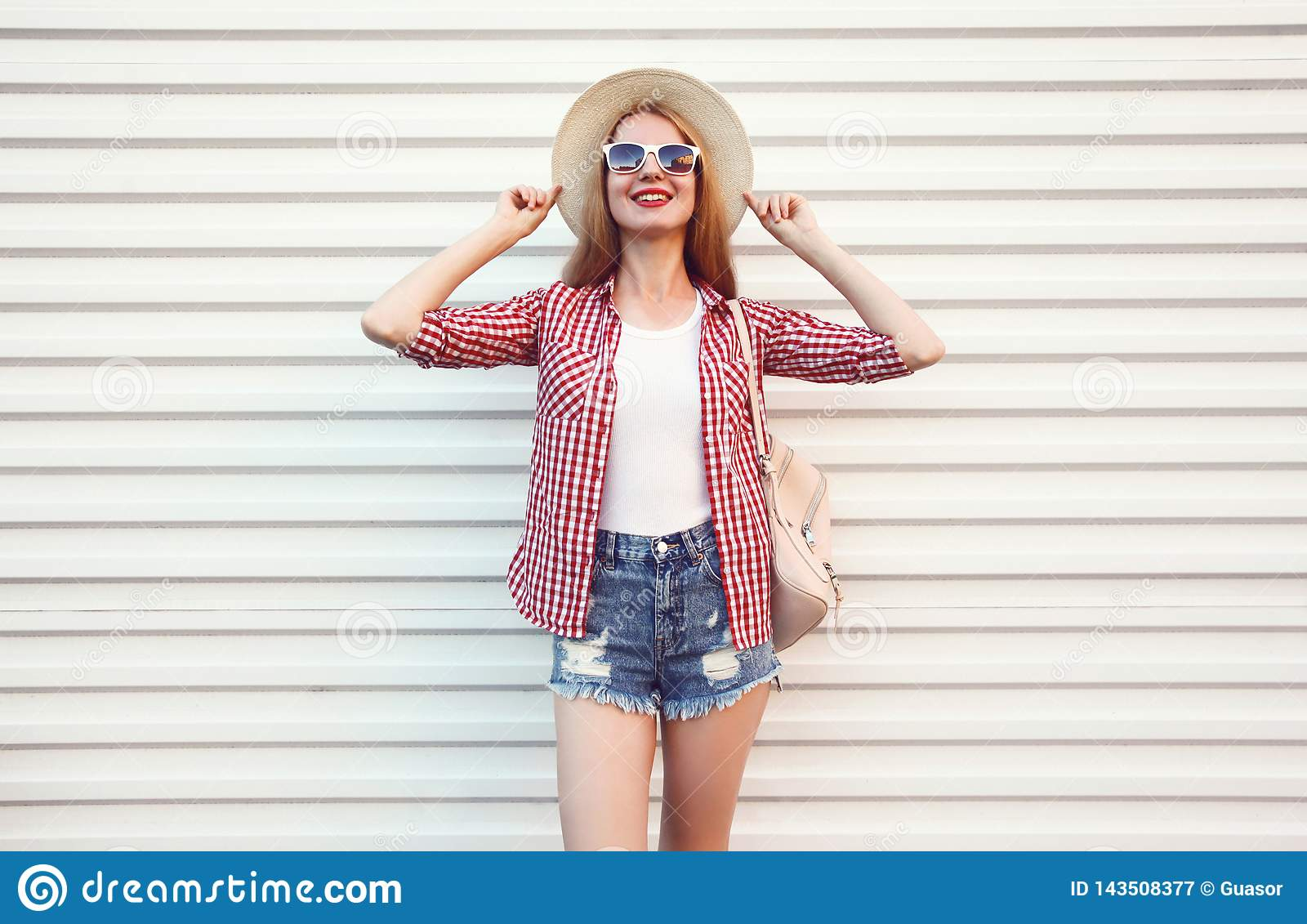 Happy smiling young woman posing in summer round straw hat, checkered shirt, shorts on white wall