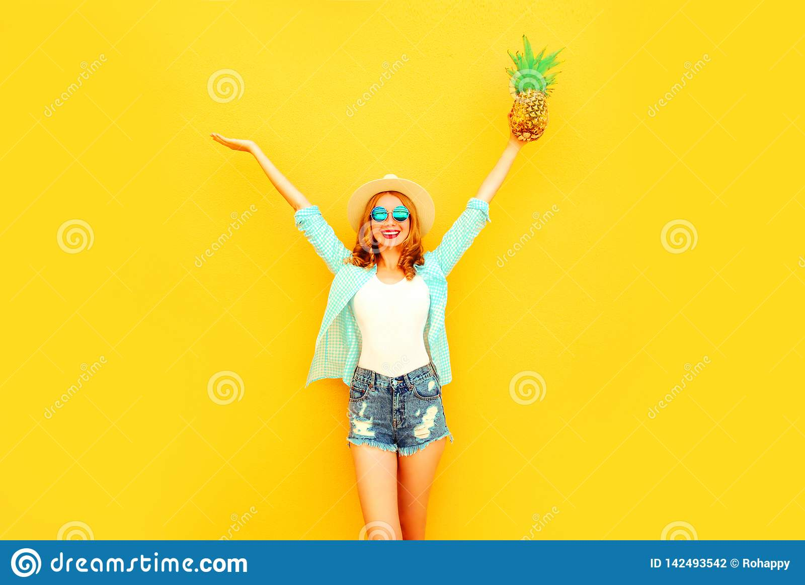 Happy smiling young woman raises her hands up with pineapple having fun in summer straw hat, sunglasses, shorts on colorful yellow