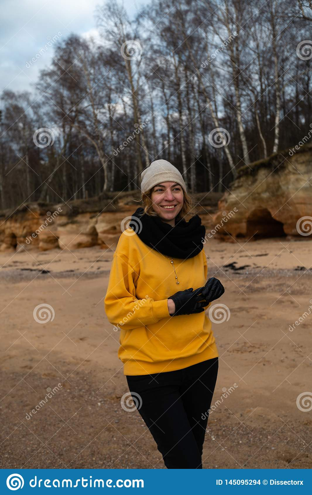 Happy sport and fashion lover enthusiast working out on a beach wearing bright yellow sweater and black gloves and a cap