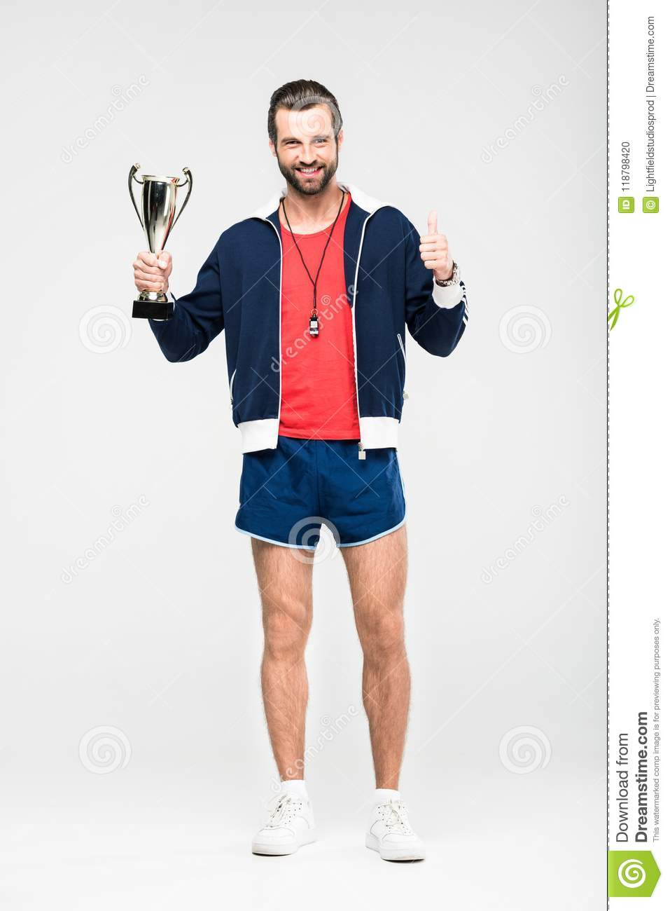 happy sportive coach with trophy cup showing thumb up,