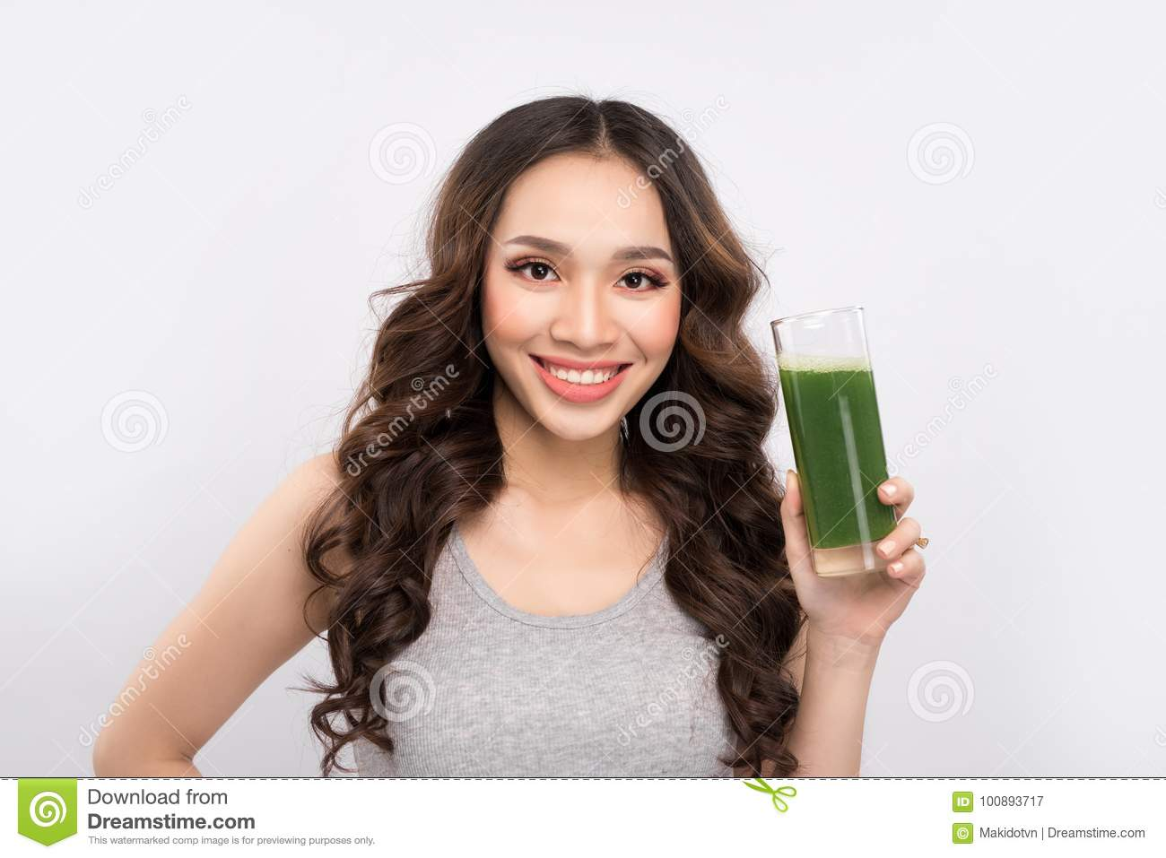 Happy sportswoman showing healthy fruit and vegetables drink.