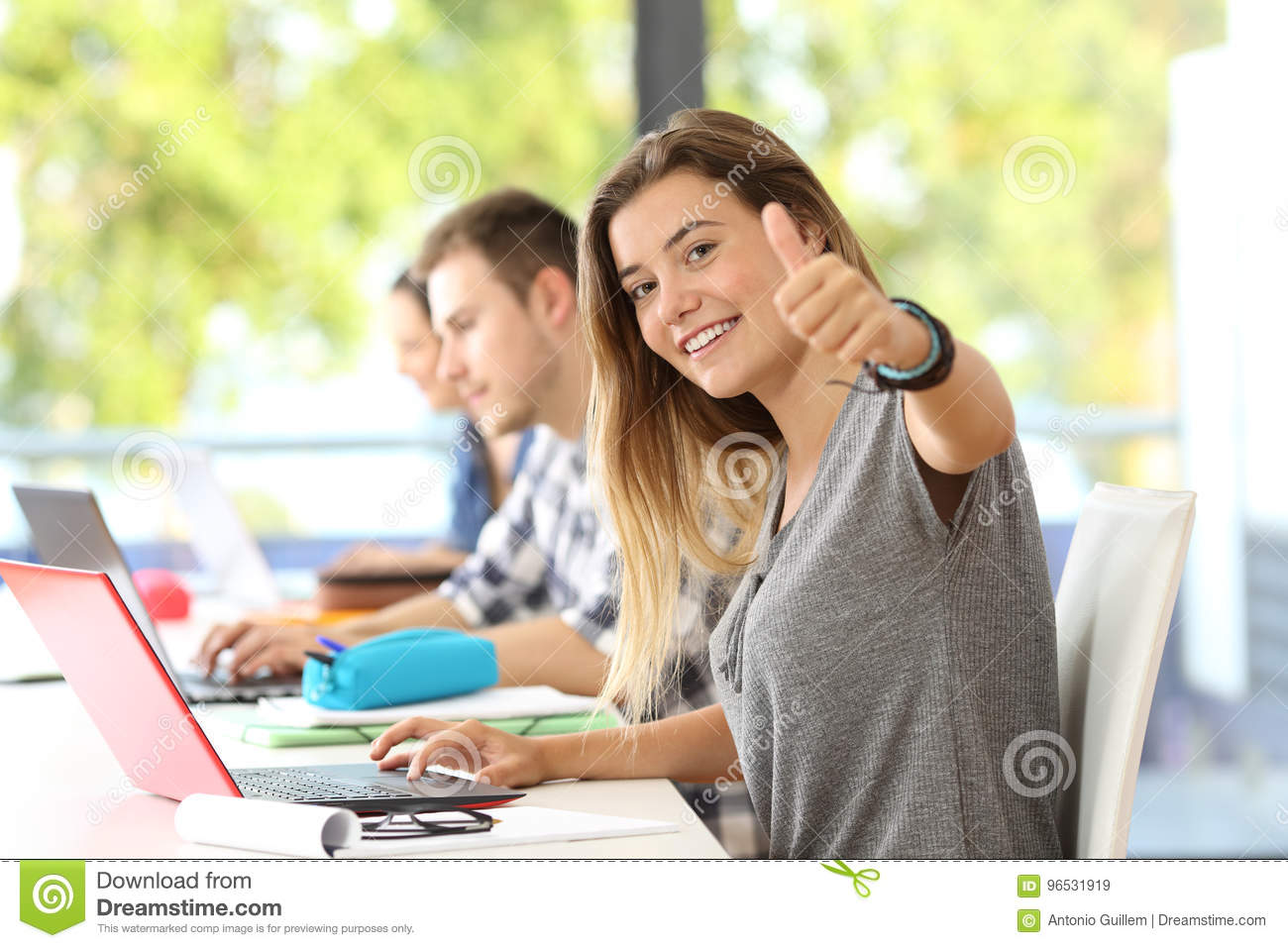 Happy student with thumbs up in a classroom