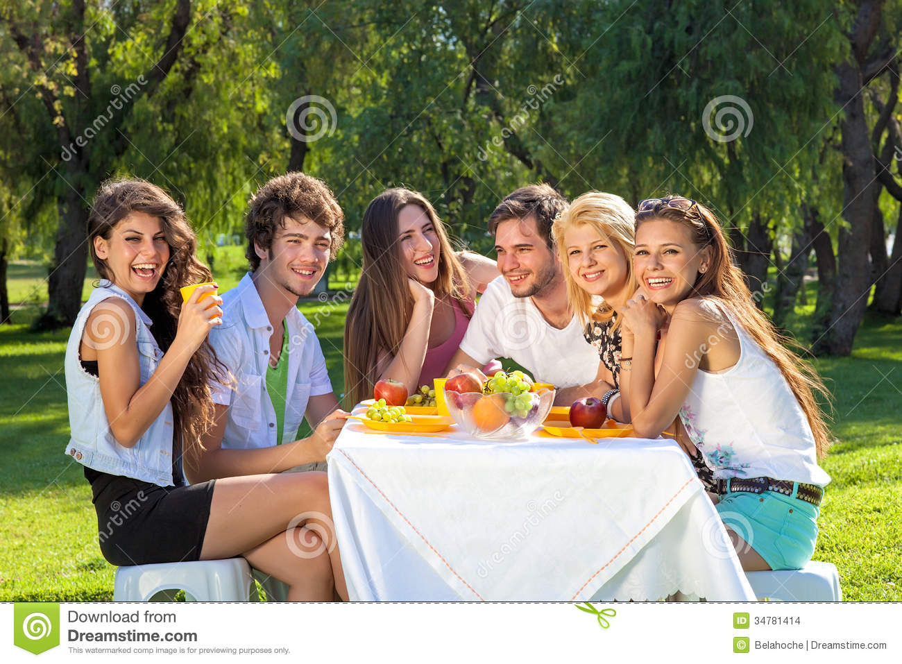 Happy students full of vitality eat a fruity meal stock for Meal outdoors