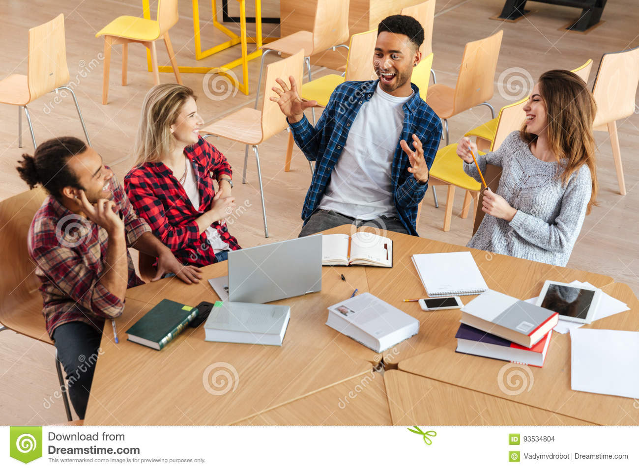 happy students sitting in library talking with each other stock