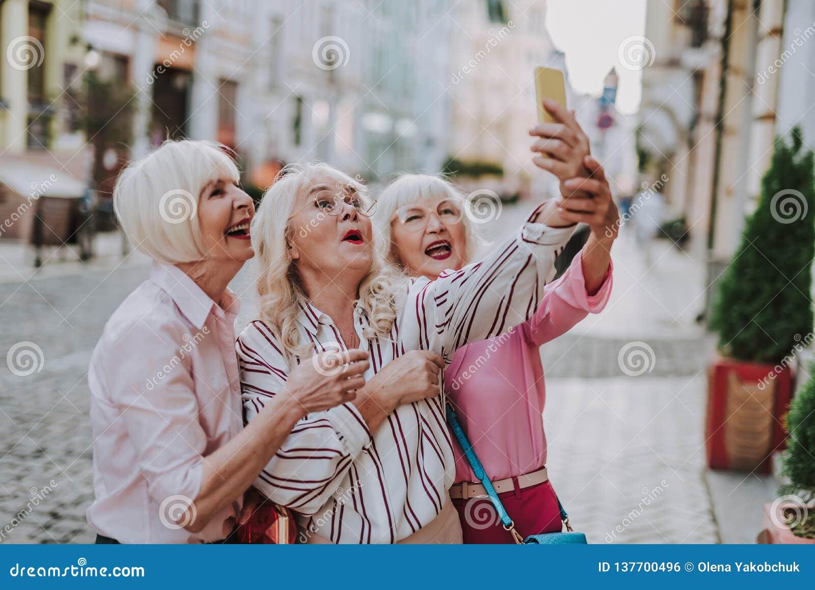 Three funny old ladies making selfie together