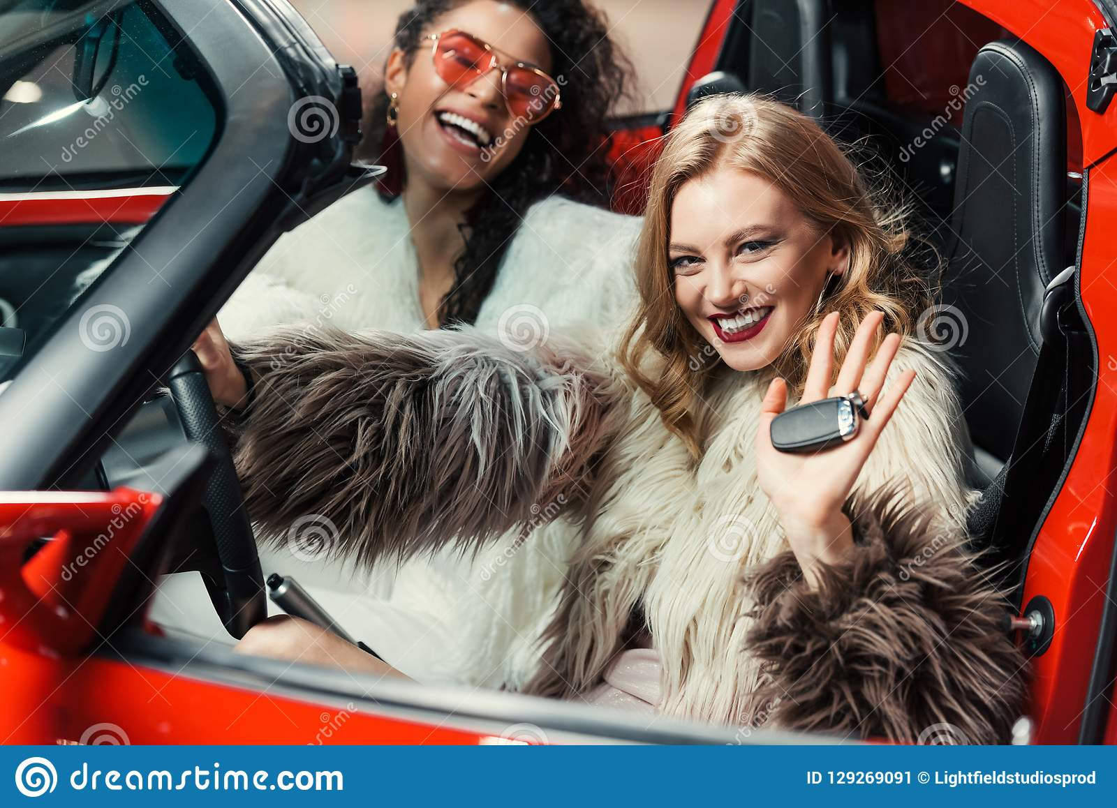 Happy Stylish Multiethnic Women In Fur Coats Holding Car Keys While Sitting In Luxury Red Stock Image Image Of Attractive Beautiful 129269091