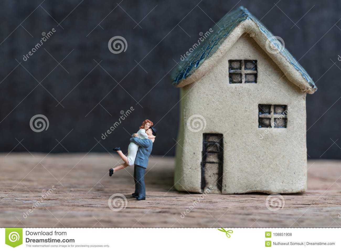 Happy success marriage love life concept, miniature lovely couple husband and wife with small house on wooden table and black