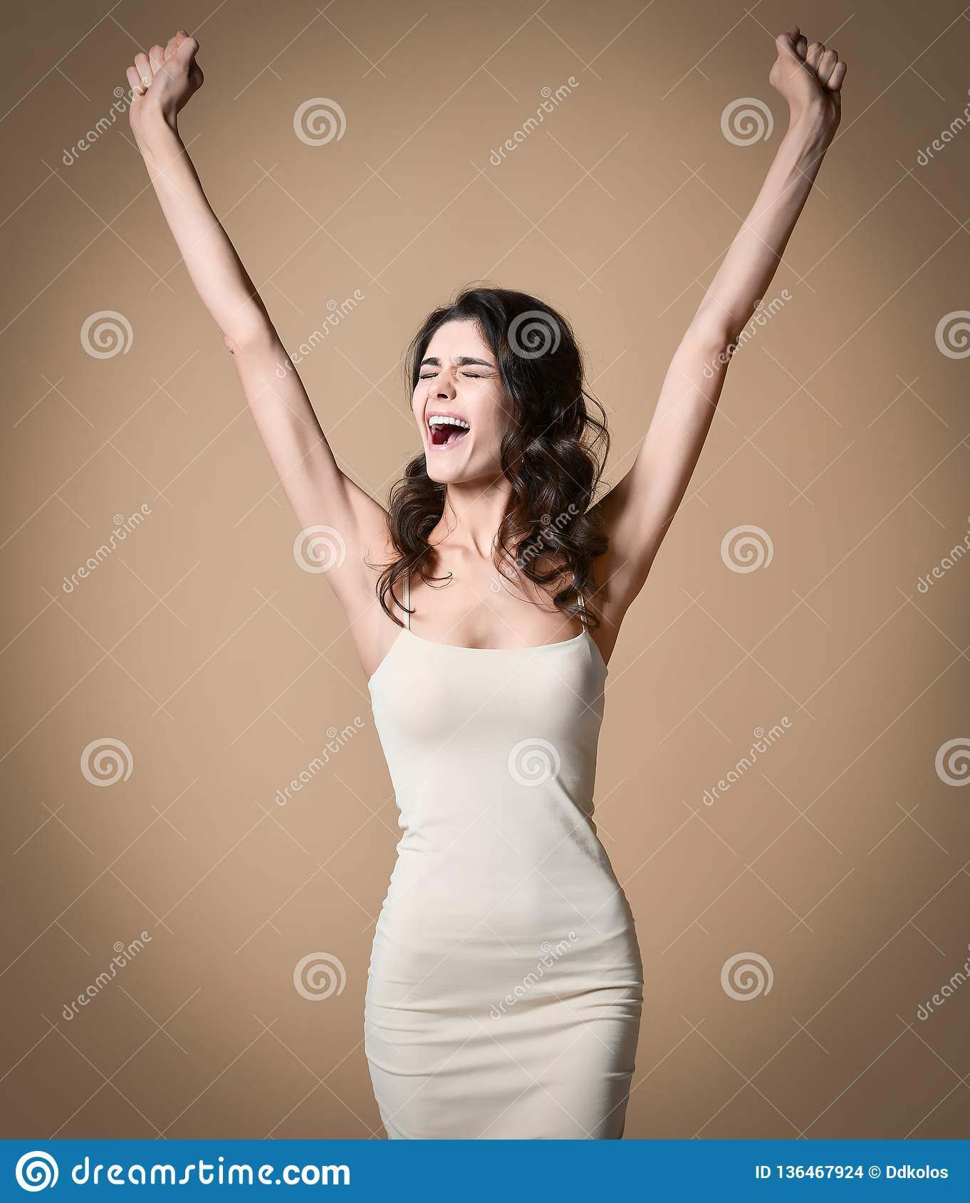 Happy successful young woman with raised hands shouting and celebrating success