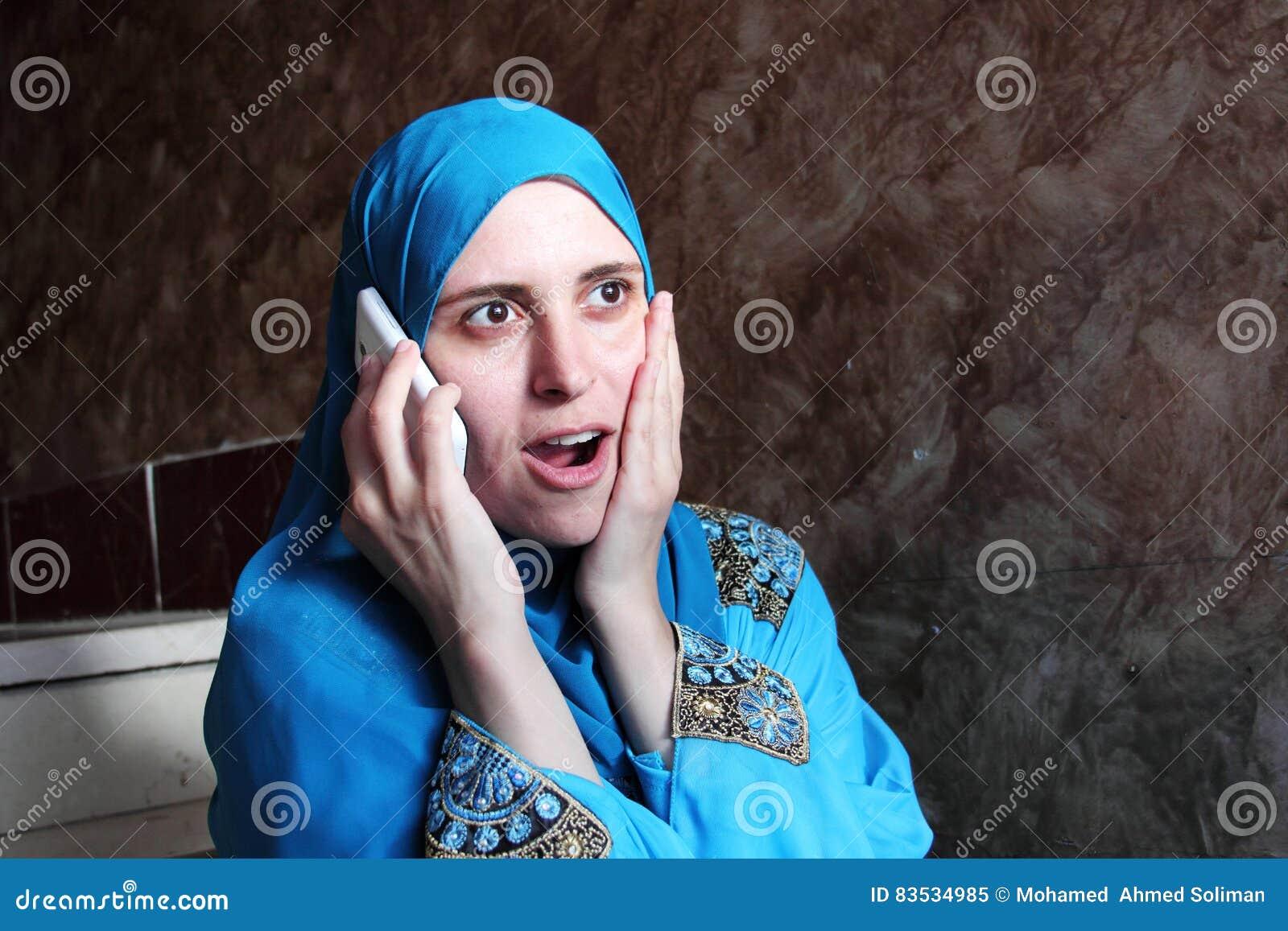 Happy surprised arab muslim woman with mobile