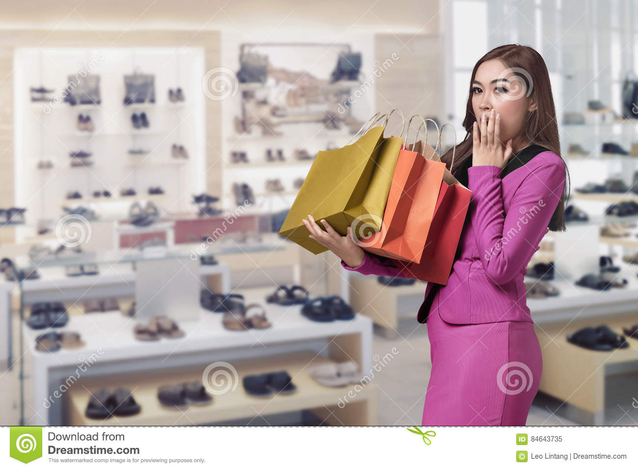 Happy surprised asian business woman with shopping bag in her ha