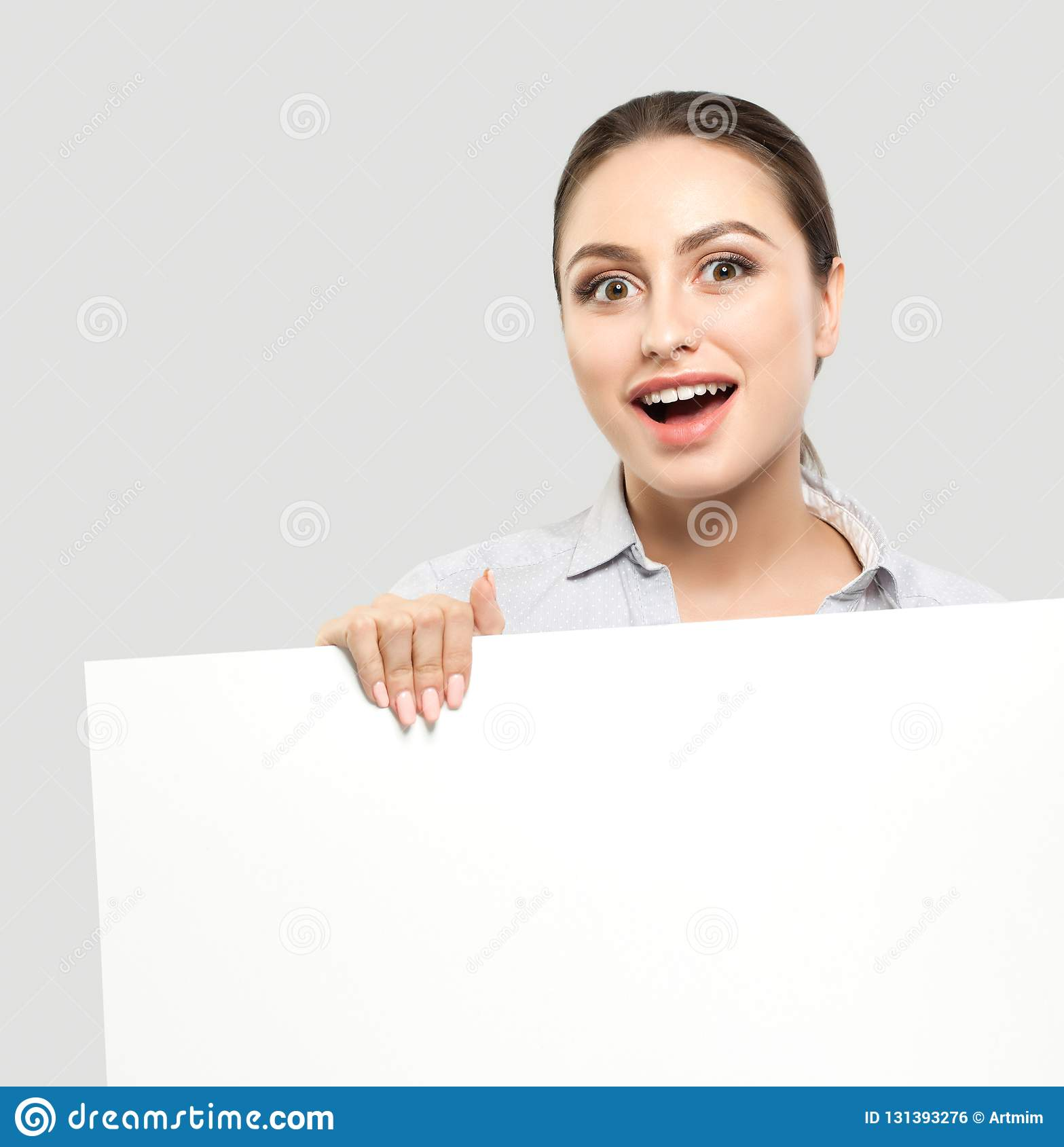 Happy surprised businesswoman with white empty board background. Young cheerful woman, business and education concept