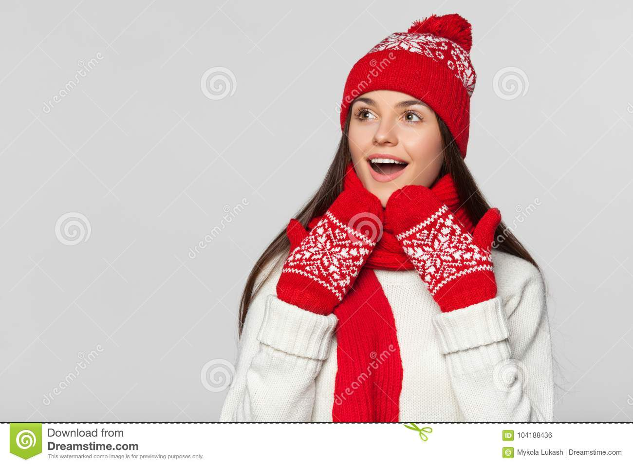 dfff5dd1a8575 Happy surprised woman looking sideways in excitement. Excited christmas girl  wearing knitted warm hat and scarf