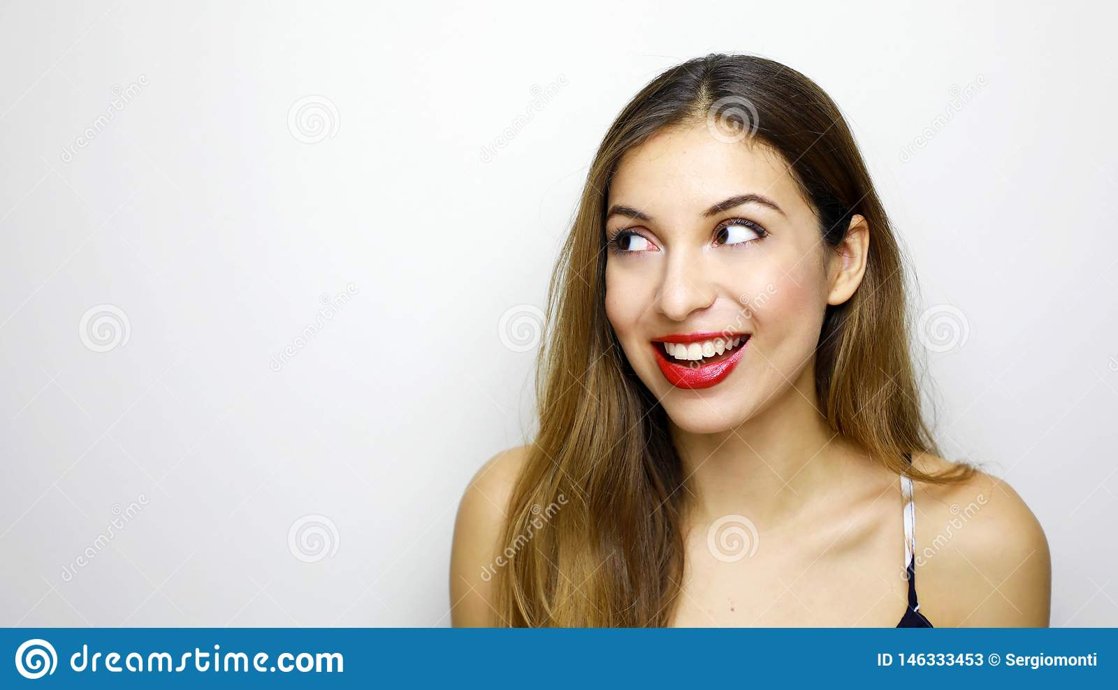 A happy surprised woman looking to the side at copy space isolated on white background