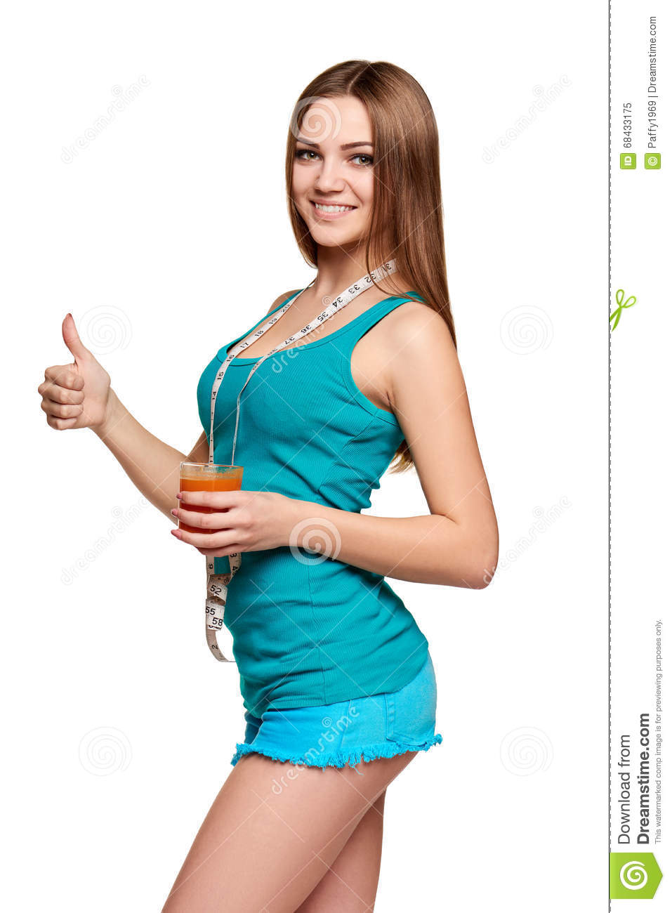 Happy girl holding a glass of carrot juice, with measurement tape over her  neck gesturing thumb up, over white background