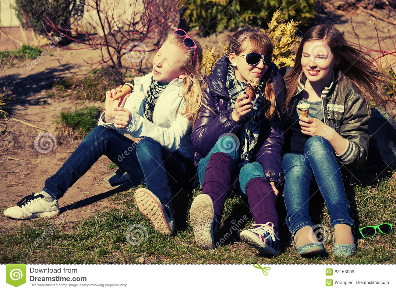 Group of happy teen girls eating an ice cream outdoor