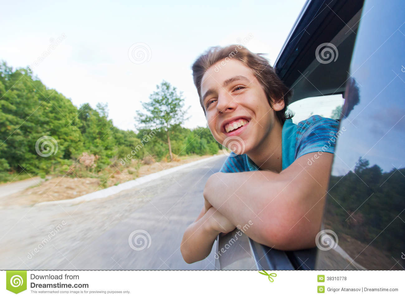 Happy Teenage Boy Leaning Out Of A Car Window Stock Photo