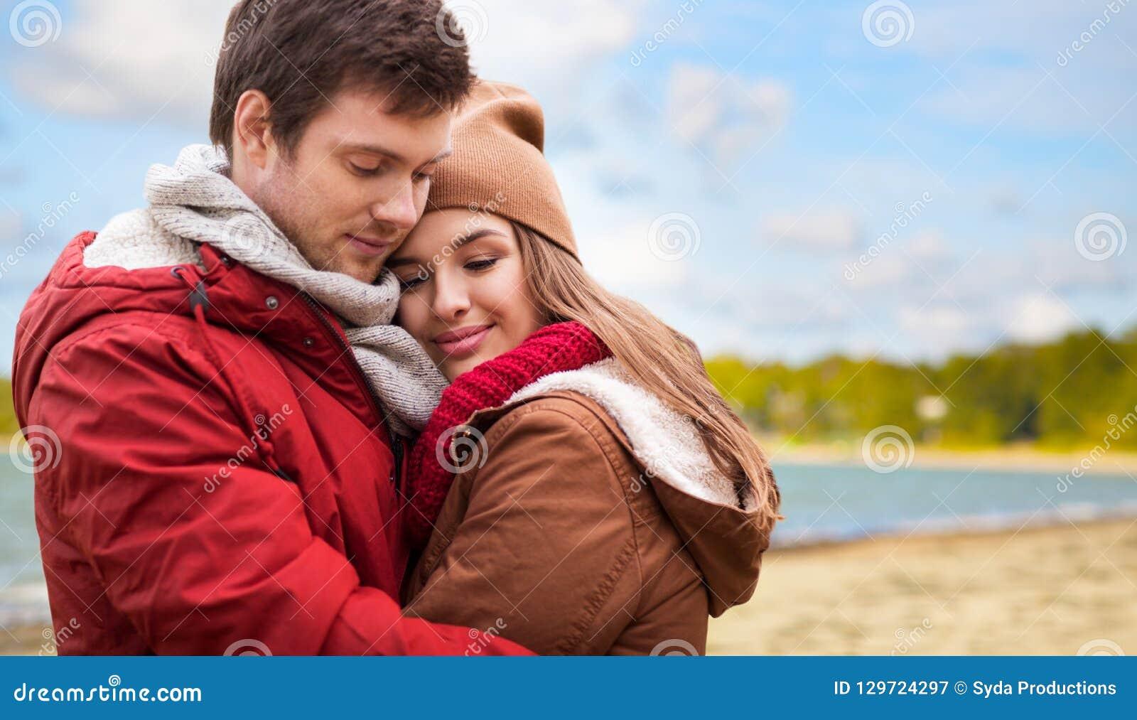 Happy teenage couple hugging over autumn beach