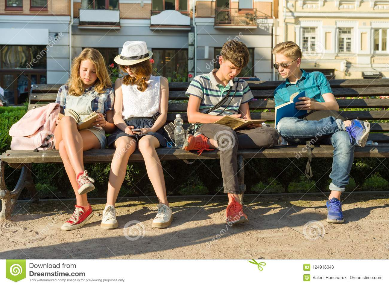 Happy 4 teenage friends or high school students are having fun, talking, reading phone, book. Friendship and people concept, city