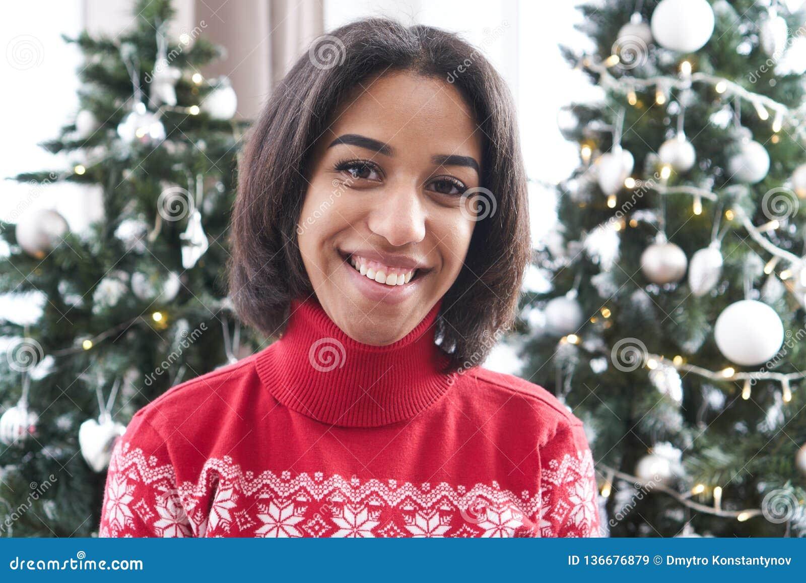Happy teenage girl in front of Christmas tree
