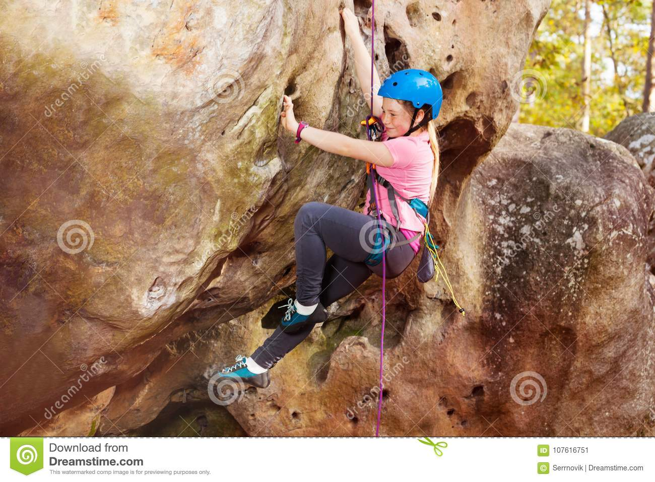 Happy teenage girl rock climbing in forest area