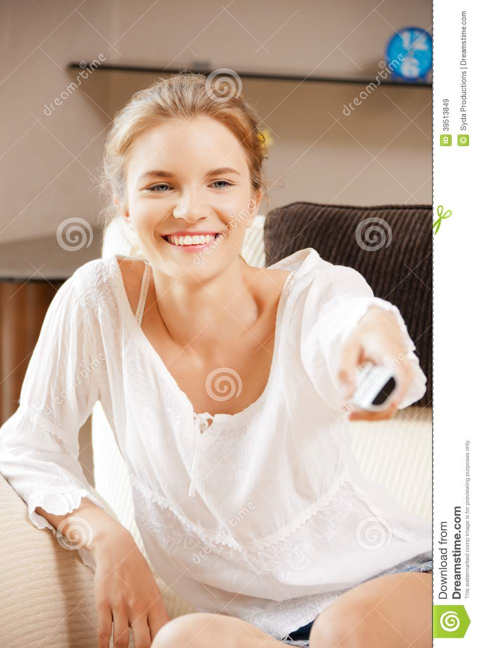 Happy teenage girl with TV remote