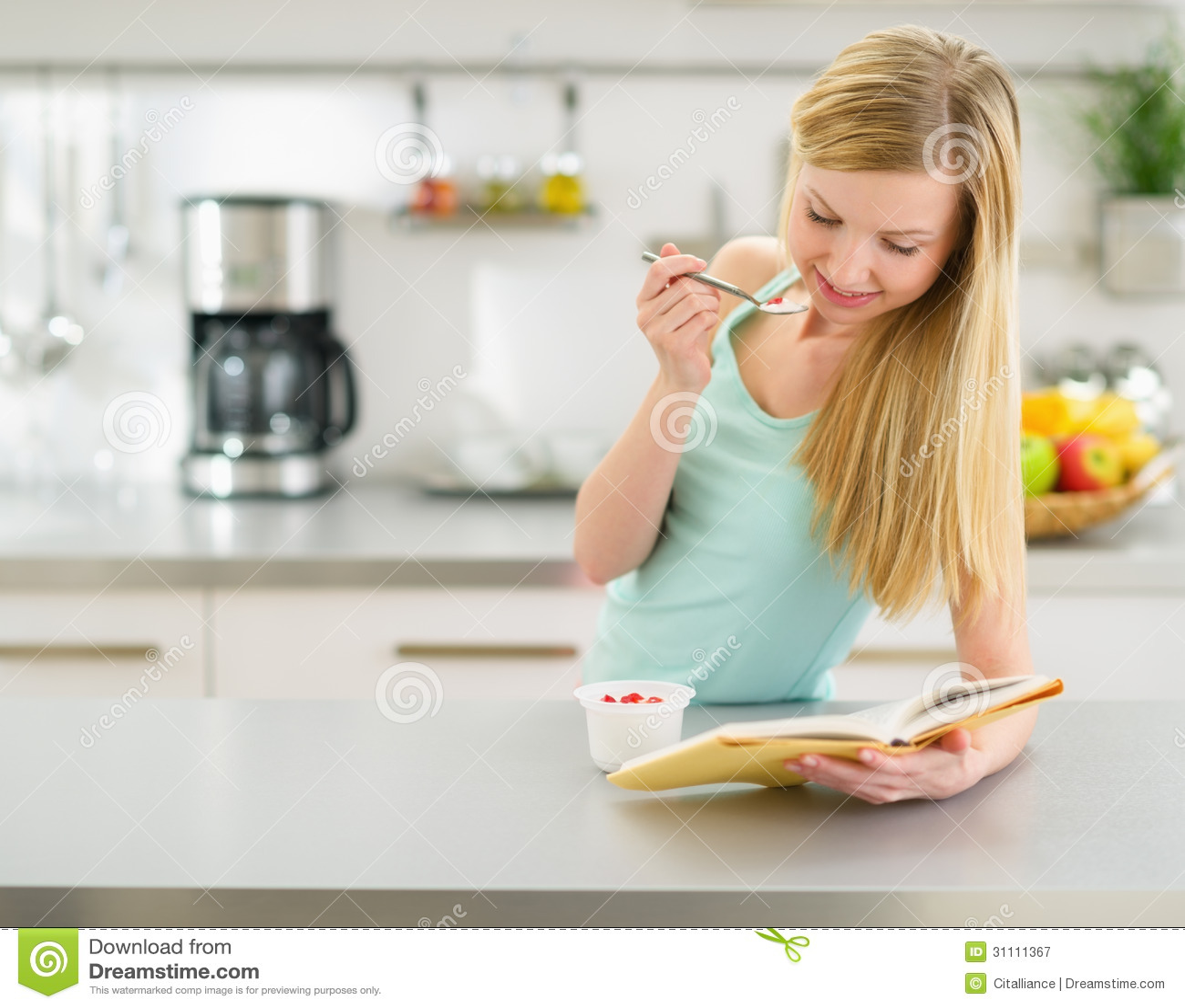 Happy Girl Kitchen: Happy Teenager Girl Reading Book And Eating Yogurt Royalty