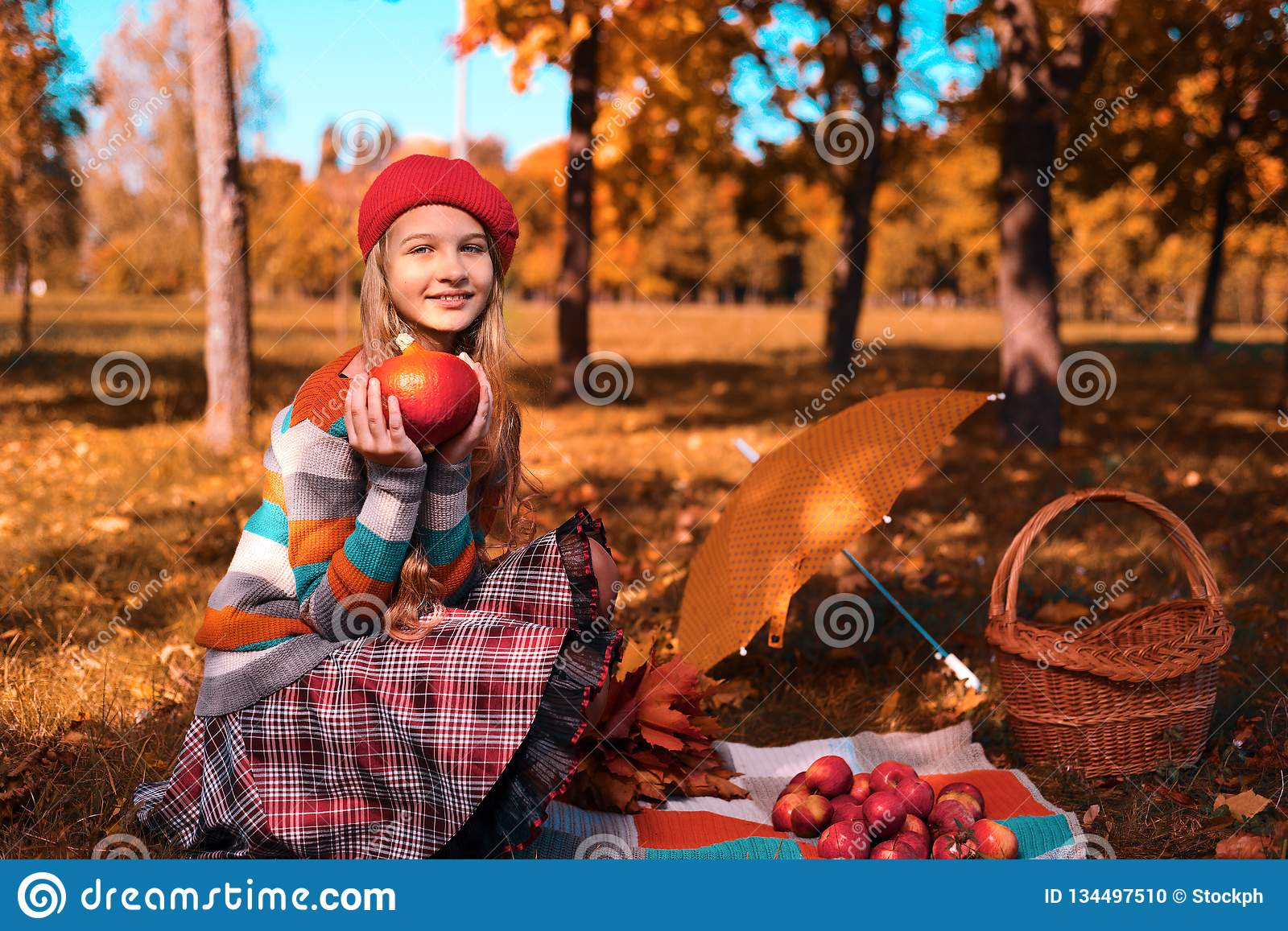 Happy teenager smiling. Autumn portrait of beautiful young girl in red hat