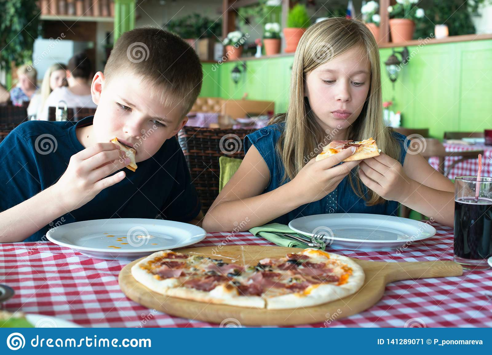 Happy teenagers eating pizza in a cafe. Friends or siblings having fun in restaurant