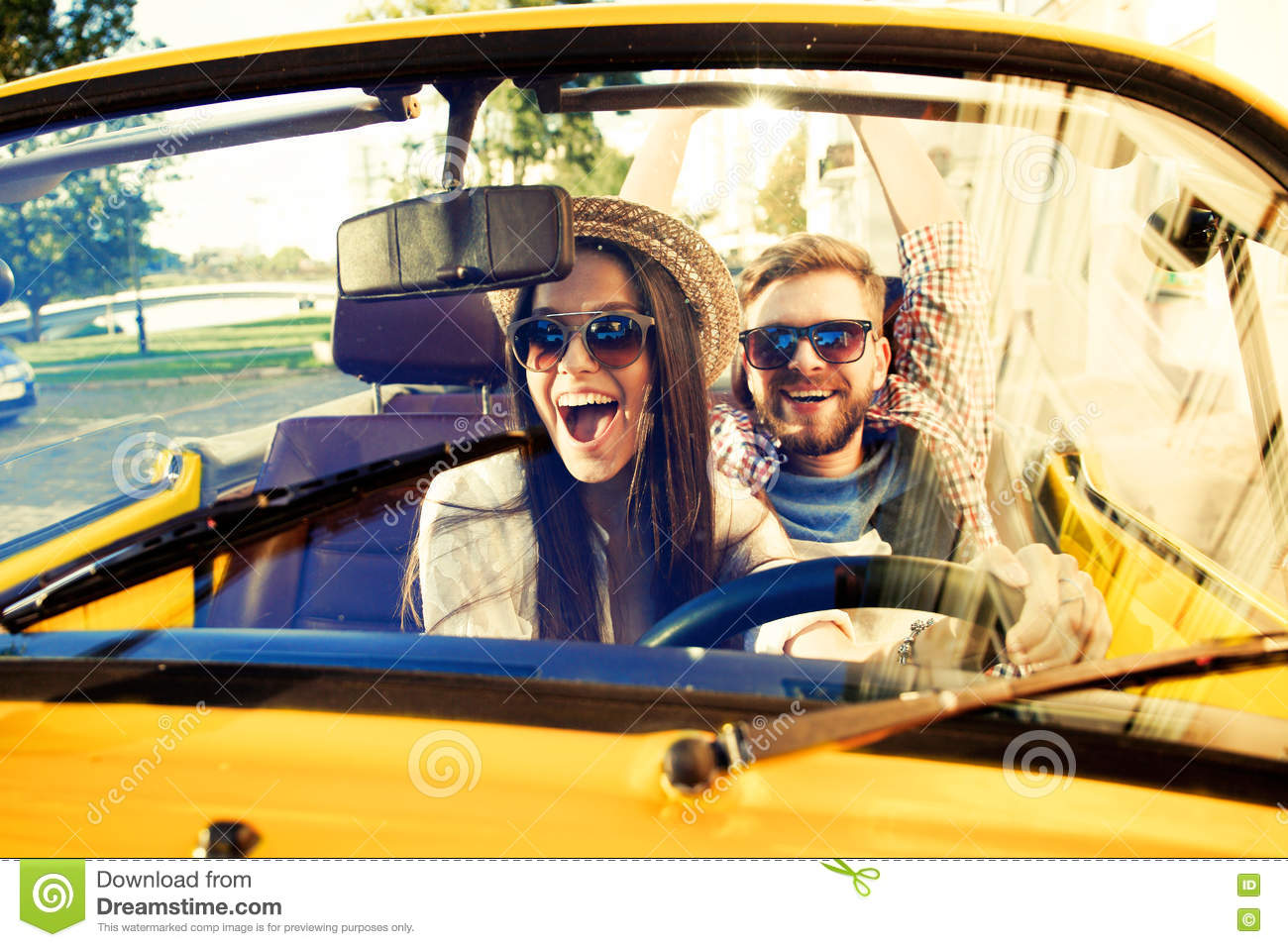 Happy to travel together. Joyful young couple smiling while riding in onvertible