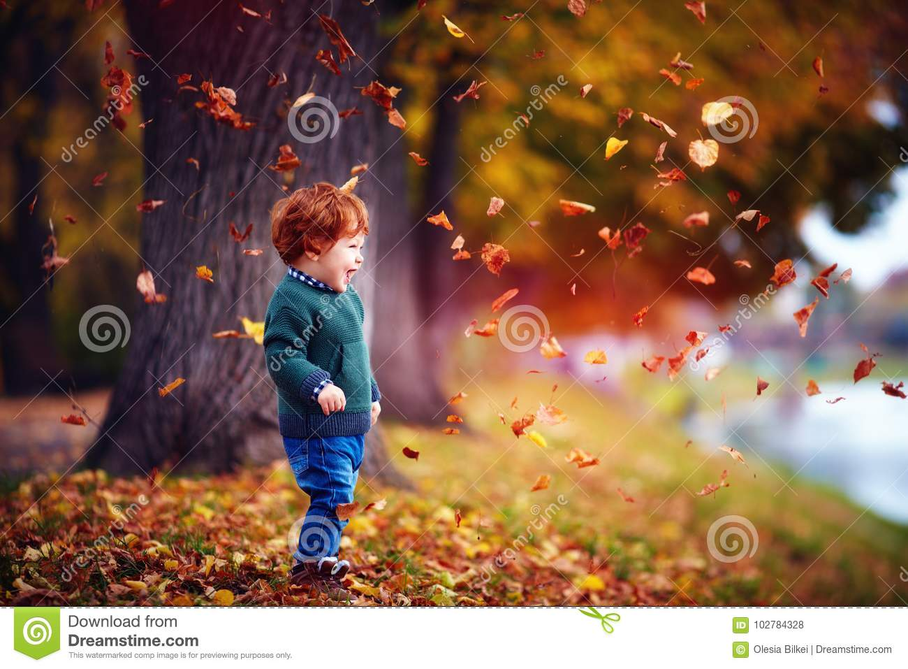 happy redhead toddler baby boy having fun, playing with fallen leaves in autumn park