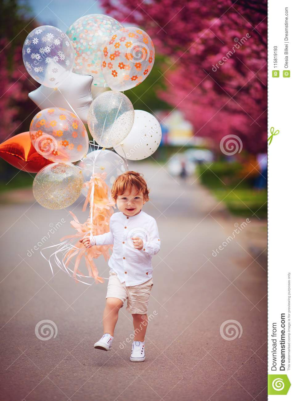 Happy toddler boy running the spring street with the bunch of air balloons