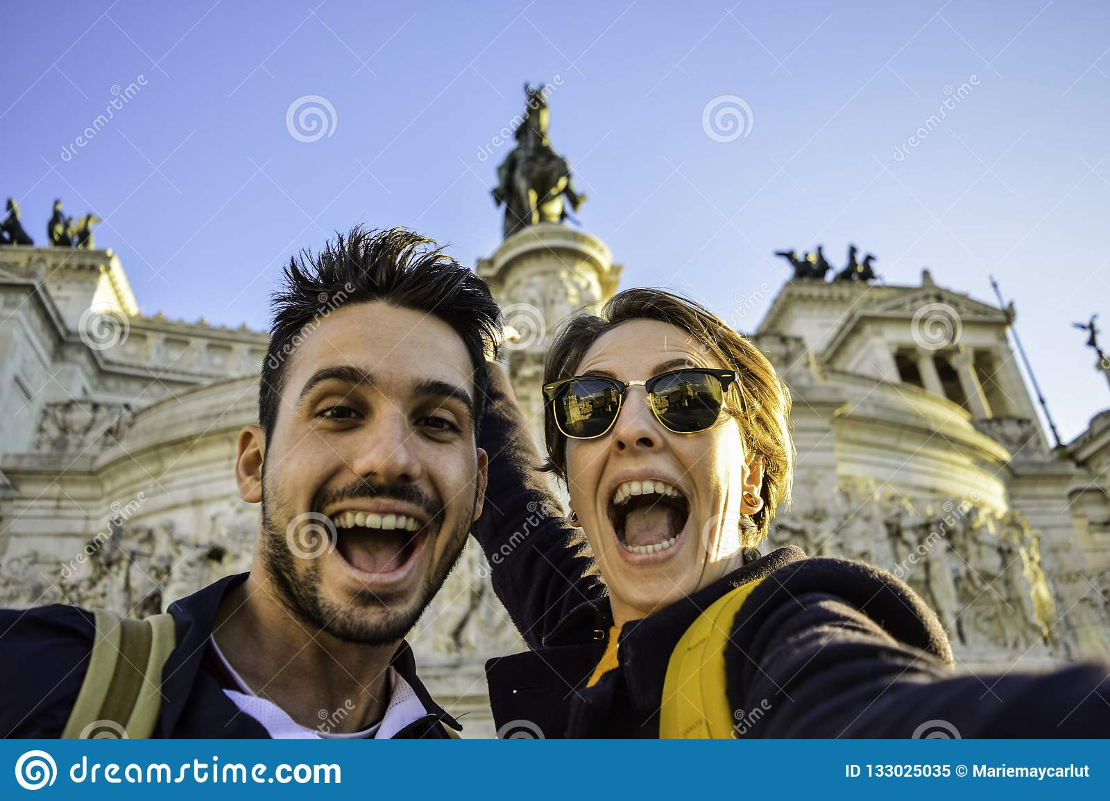 Happy travel couple taking selfie with the smartphone in famous landmark in la Piazza Venezia, Rome, Italy
