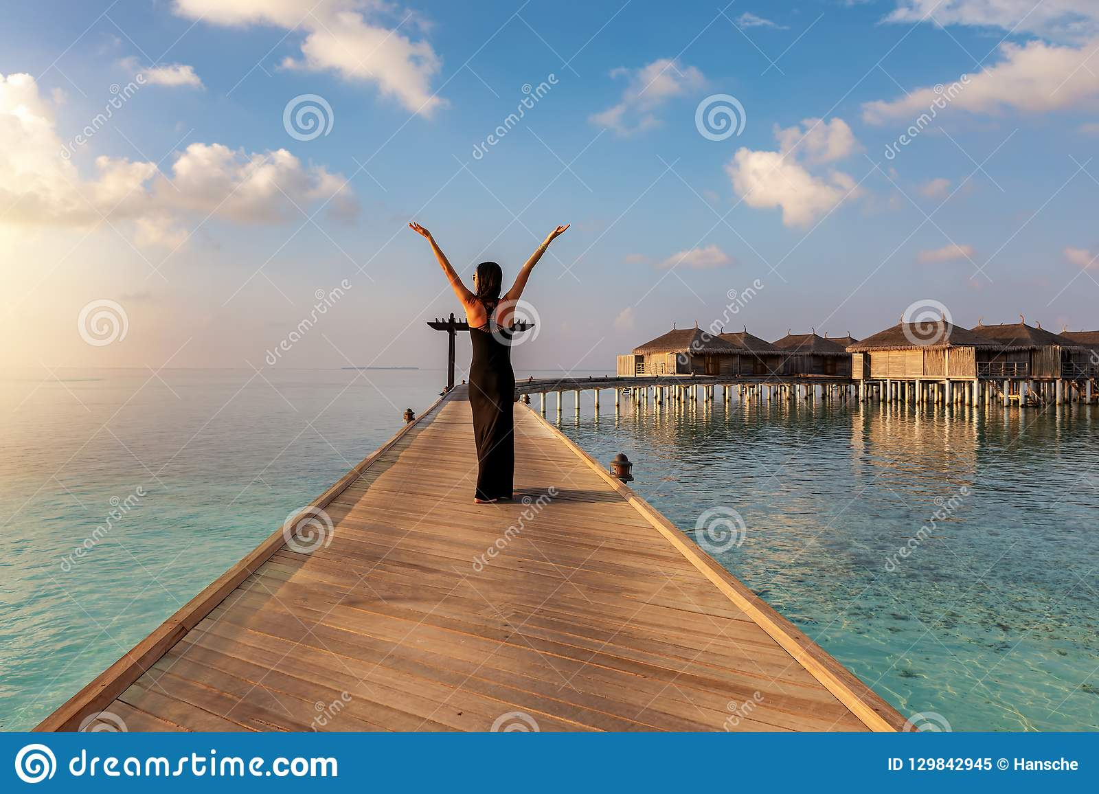 Woman walks on a wooden jetty in the Maldives