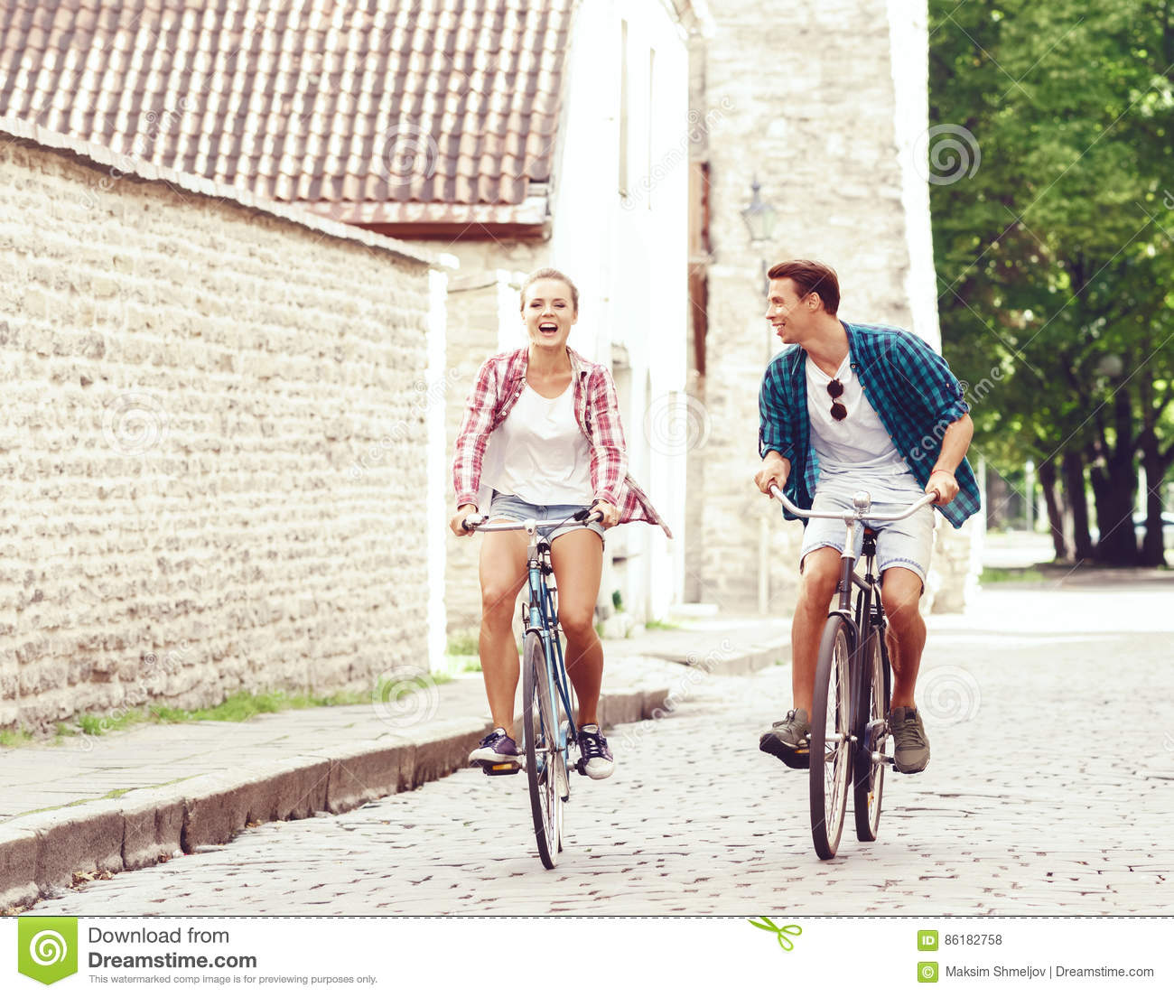 Young Couple Of Hipsters Riding A Bicycle Date In Old Town Love