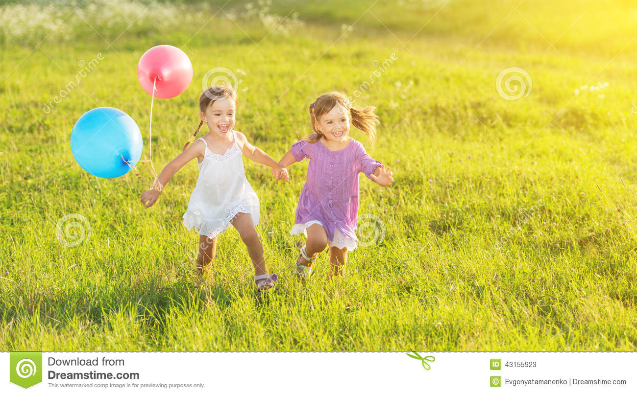 Happy twin sisters running around laughing and playing with balloons in summer