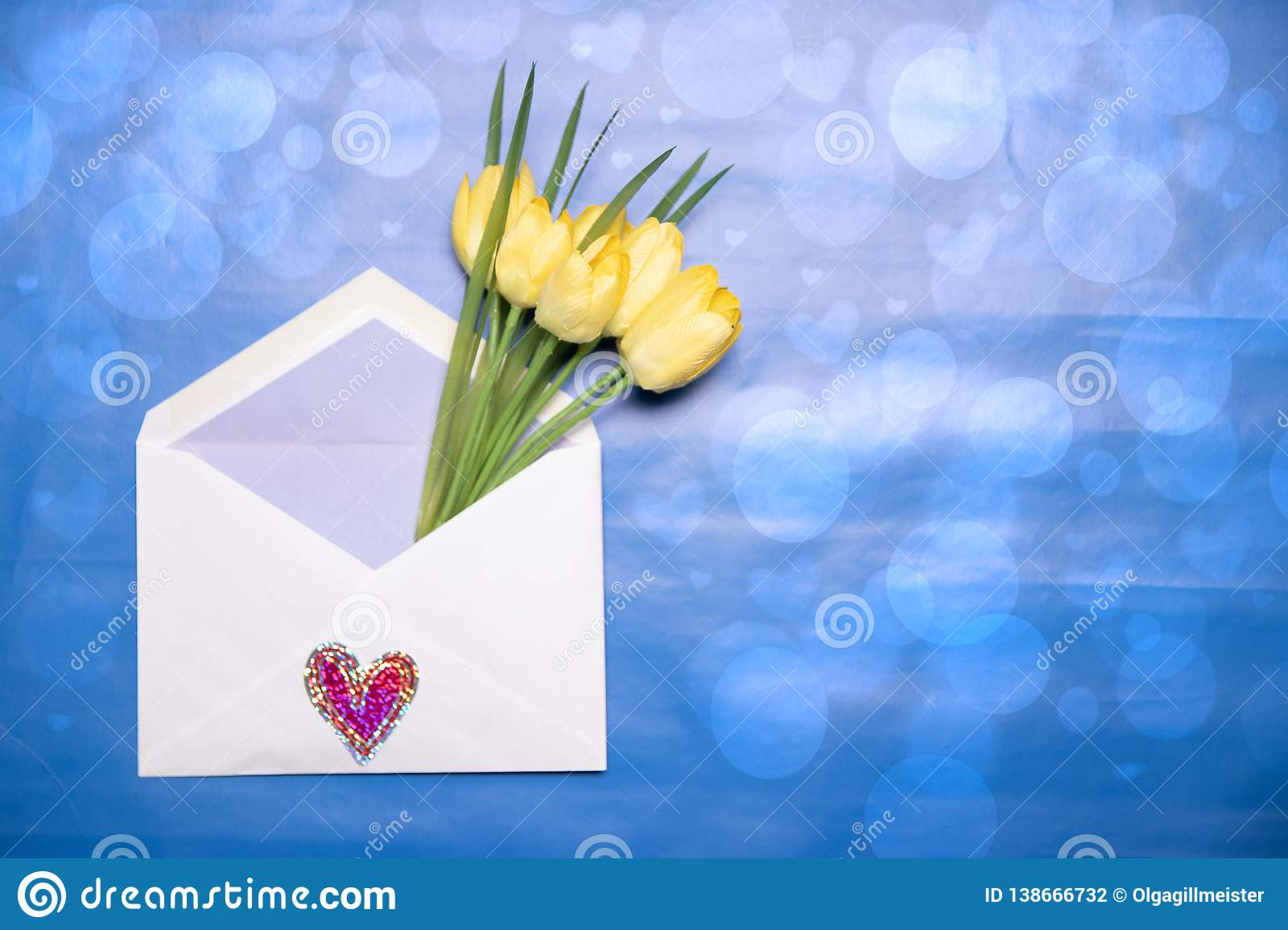Happy Valentine or Mothers Day background. Beautiful bouquet of yellow tulips in an open envelope with a hearts symbol lying on a