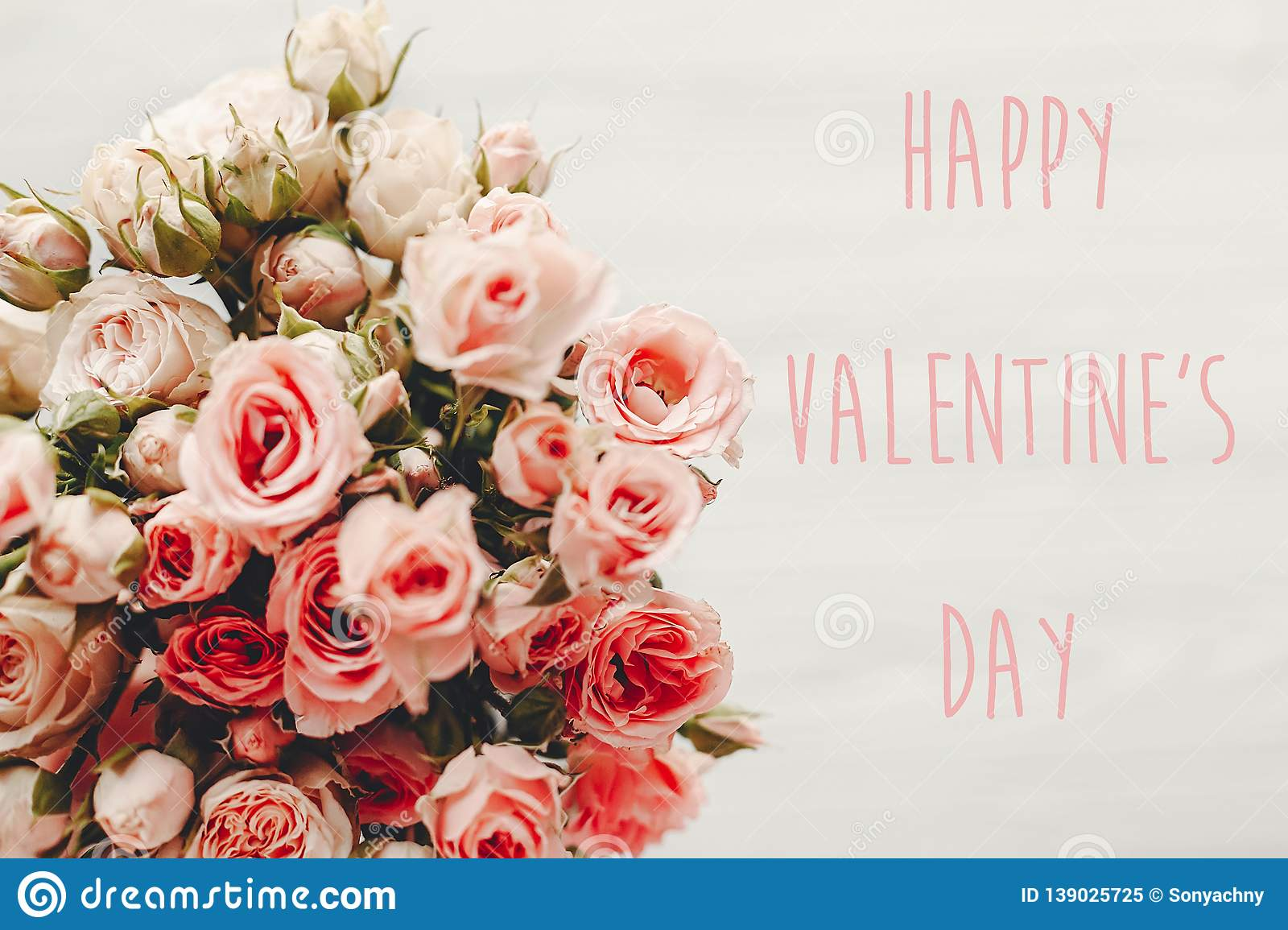 Happy Valentine`s Day text sign on pink roses bouquet on white background, top view. Valentines day floral greeting card