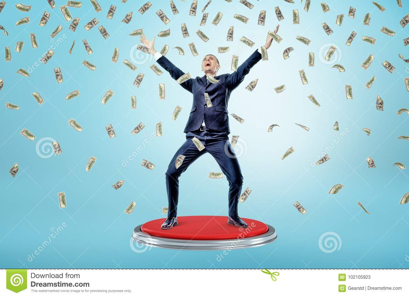 A happy and victorious businessman stands on a giant red button under many falling 100 dollar bills.