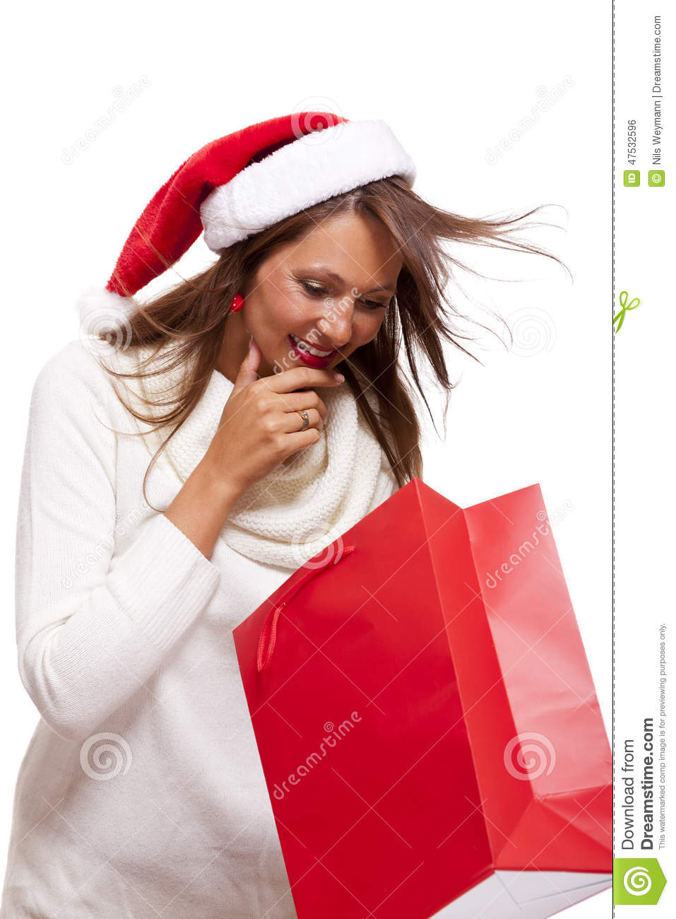 836ee36b021b5 Happy vivacious Christmas shopper wearing a red Santa hat holding up a  colorful red shopping bag with a beautiful beaming smile